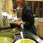 photo of Christina Lundahl stirring butternut squash cider soup with Sheri Geoffreys taking photos in the background