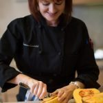 photo of Christina Lundahl scooping our squash for butternut squash cider soup