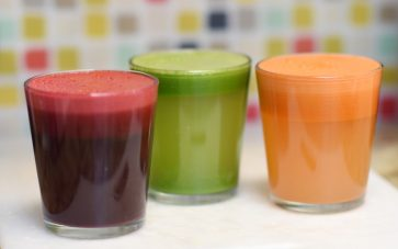 photo of three juices - red juice, green juice, and orange juice - for delicious juicing recipes