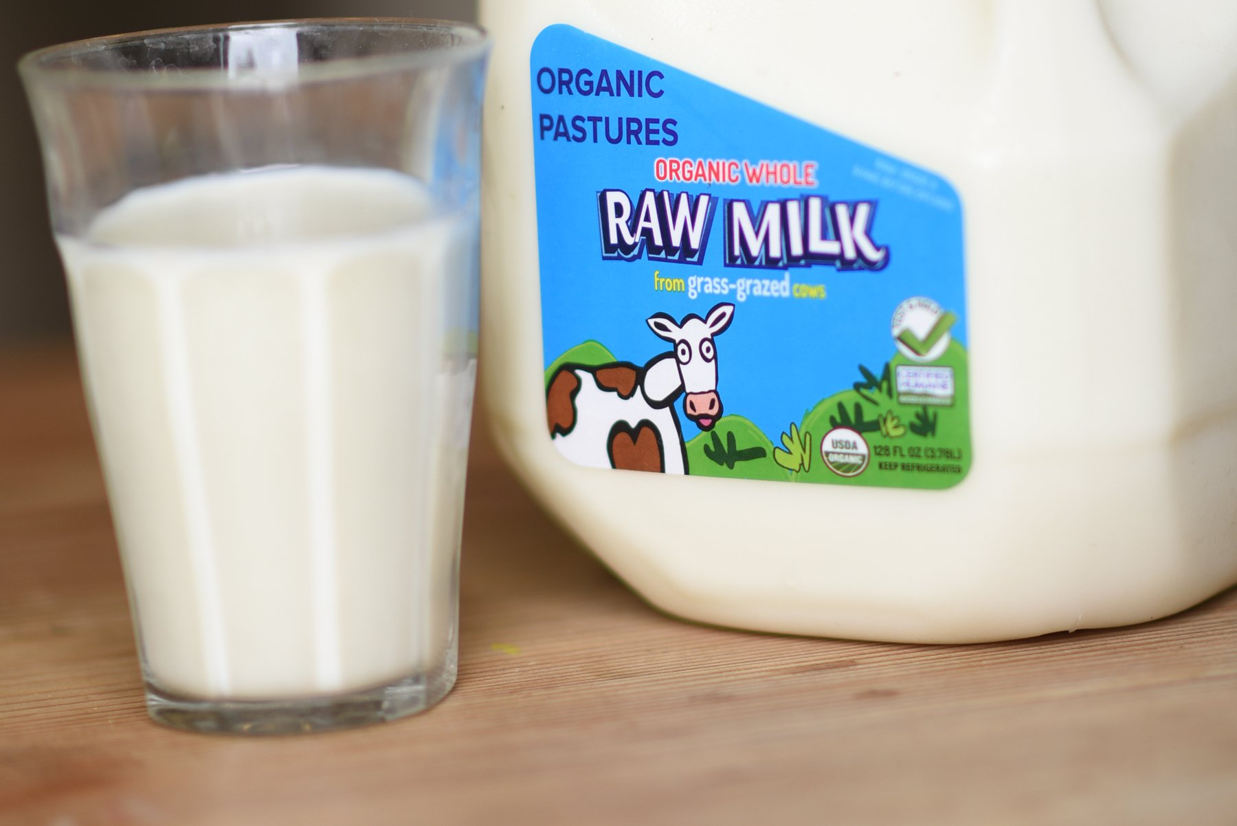 photo of a glass and gallon of raw milk
