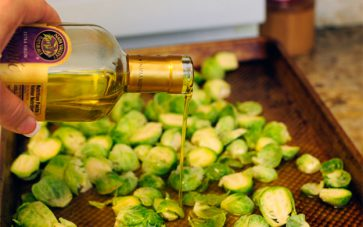photo of brussels sprouts on baking sheet with person pouring olive oil over them