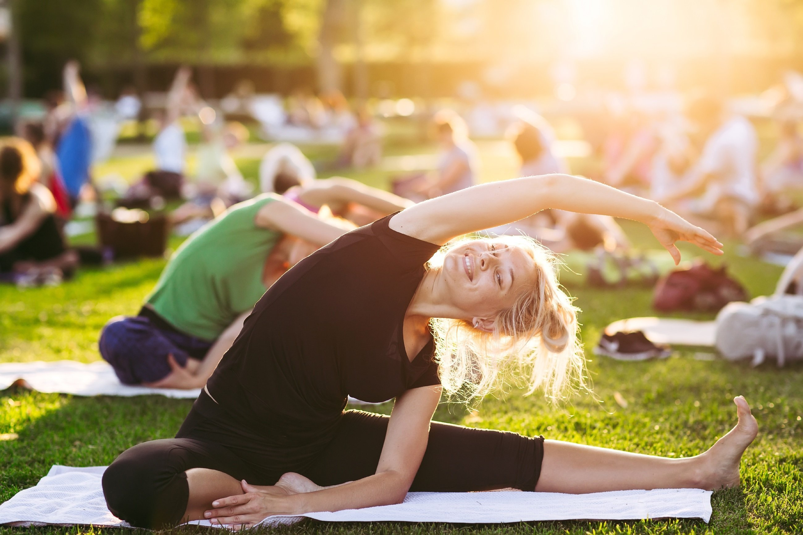 photo of women stretching in outdoor fitness class